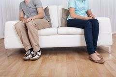 Brother and sister arguing. Brother and sister have had an argument and are sitting at opposite ends of a sofa Stock Photography