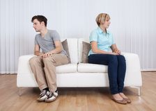 Brother and sister arguing. Brother and sister have had an argument and are sitting at opposite ends of a sofa Royalty Free Stock Image