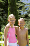 Brother and sister (6-10) arm in arm, in swimsuits, smiling, portrait Stock Photography