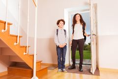 Brother and sister arriving home after school. Full-length portrait of age-diverse brother and sister arriving home after school, opening the front door royalty free stock images