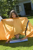 Brother and sister (8-10) assembling tent on garden lawn, girl sitting on top of boy, holding orange outer tent canvas, smiling, p Stock Images