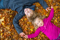 Brother and sister in autumn foliage Stock Photos