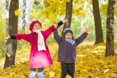 Brother and sister in autumn park indulge in throwing up yellow leaves, royalty free stock images