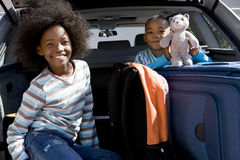 Brother and sister (6-10) in back of car with luggage, boy holding toy, smiling, portrait Royalty Free Stock Photo