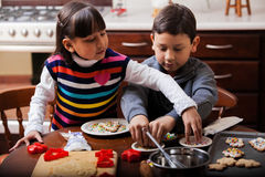 Brother and sister baking cookies Stock Photos