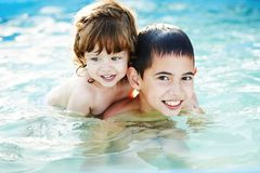 Brother and sister bathe outside in pool Royalty Free Stock Image