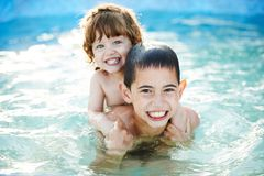 Brother and sister bathe outside in pool Stock Photos