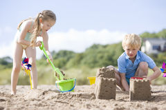 Brother and sister at beach making sand castles royalty free stock image