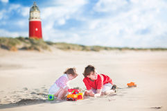 Brother and sister on the beach next to lighthouse Stock Photo