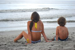 A brother and sister on beach staring at ocean. A brother and sister or boy and girl sitting on the beach in the sand with their backs to the camera as they are Stock Image
