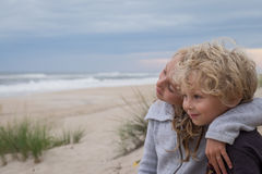 Brother and sister at beach. Young boy and girl in embrace on empty sandy beach of seashore on sunny day Royalty Free Stock Image