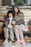 Brother and sister on a bench in front of the house in winter Stock Image