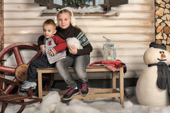 Brother and sister on a bench in front of the house in winter Royalty Free Stock Photo