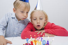 Brother and sister blowing birthday candles at table in house Royalty Free Stock Photo