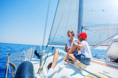Brother and sister on board of sailing yacht on summer cruise. Travel adventure, yachting with child on family vacation. Stock Photos