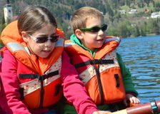 Brother and sister on a boat. Two siblings waring life-vests on a sailing on rowboat on Bled Lake, Slovenia Stock Photos