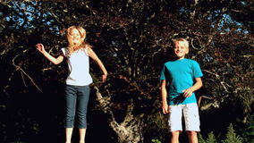 Brother and sister bouncing on a trampoline stock footage