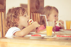 Brother and sister at breakfast Stock Images