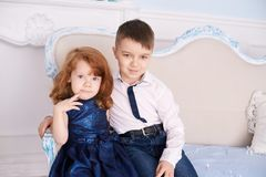 Brother and sister. Bright interior. Blue dress. Horizontally. Light background Stock Photos