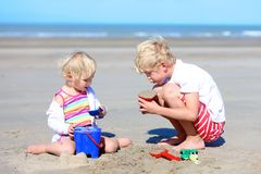 Brother and sister building sand castles on the beach Stock Image