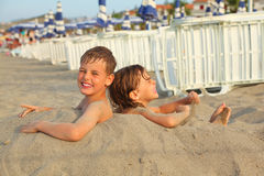 Brother and sister buried in sand on beach Stock Photos