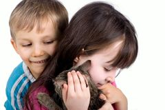 Brother And Sister With Cat. Young boy hugging his sister and the cat that his sister is holding in her arms.  Isolated on white Stock Photo