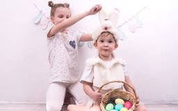 Brother and sister celebrate Easter. The boy is dressed in a rabbit costume and holds a korunzku with Easter eggs. Portrait Royalty Free Stock Image