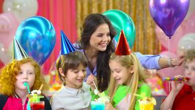 Brother and sister are celebrating birthday with mother and fiends. Brother and sister in colorful hats celebrating their birthday with mother and fiends at stock video