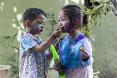 Brother and sister celebrating Holi. Brother and sister with their face smeared with colors celebrating Holi festival in India Royalty Free Stock Image