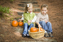 Brother and Sister Children Sitting on Wood Steps with Pumpkins Royalty Free Stock Images