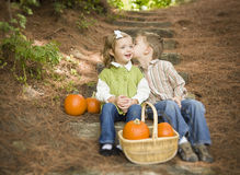 Brother and Sister Children on Wood Steps with Pumpkins Whisperi. Adorable Brother and Sister Children Sitting on Wood Steps with Pumpkins Whispering Secrets or Royalty Free Stock Photos