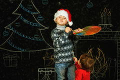 Brother and sister on Christmas background , playing with a palette and brushes .Merry Christmas Royalty Free Stock Photo