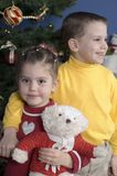 Brother and Sister by a Christmas tree. In front of a Christmas tree stands a brother with his arm around his sister who is holding a teddy bear Royalty Free Stock Photos