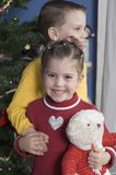 Brother and Sister by a Christmas tree. In front of a Christmas tree stands a brother with his arm around his sister who is holding a teddy bear Royalty Free Stock Images