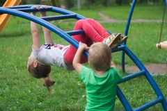 Brother and sister climb and hang on a metal ladder royalty free stock photo