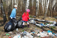 Brother and sister collect trash in park. Back of brother and sister with black bags collect trash in park at spring Stock Image