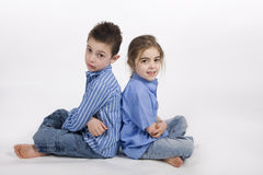 Brother and sister complicity. 7 year old boy and his 5 year old sister sitting back to back Royalty Free Stock Images