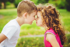 Brother and sister confronted foreheads in summer park. Royalty Free Stock Images