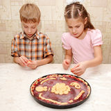 Brother and sister cooking a pie Royalty Free Stock Photo