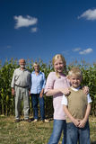 Brother and sister (7-11) by corn field, grandparents in background, smiling, portrait, low angle view Royalty Free Stock Photo