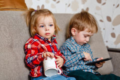 Brother and sister on the couch with a mug and a cell phone Stock Image