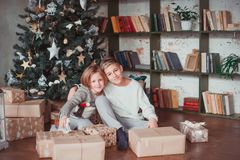 Brother and sister in a cozy room next to the Christmas tree holding gifts. New year concept royalty free stock images