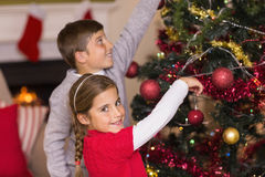 Brother and sister decorating the christmas tree together. At home in the living room Stock Photos