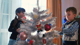 Brother and sister decorating Christmas tree. Two adorable children decorating Christmas tree. Winter holidays Christmas and New Year stock footage
