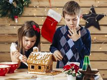 Brother and sister decorating gingerbread house royalty free stock photo