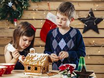 Brother and sister decorating gingerbread house. Photo of a young brother and sister decorating a gingerbread house at home just before Christmas stock image