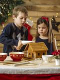 Brother and sister decorating gingerbread house. Photo of a young brother and sister decorating a gingerbread house at home just before Christmas royalty free stock photos