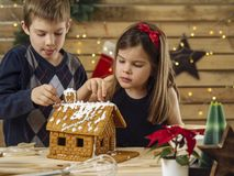 Brother and sister decorating gingerbread house. Photo of a young brother and sister decorating a gingerbread house at home just before Christmas royalty free stock image