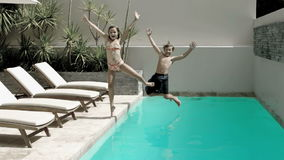 Brother and sister diving into the swimming pool Royalty Free Stock Images