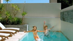 Brother and sister diving into the swimming pool Royalty Free Stock Photo